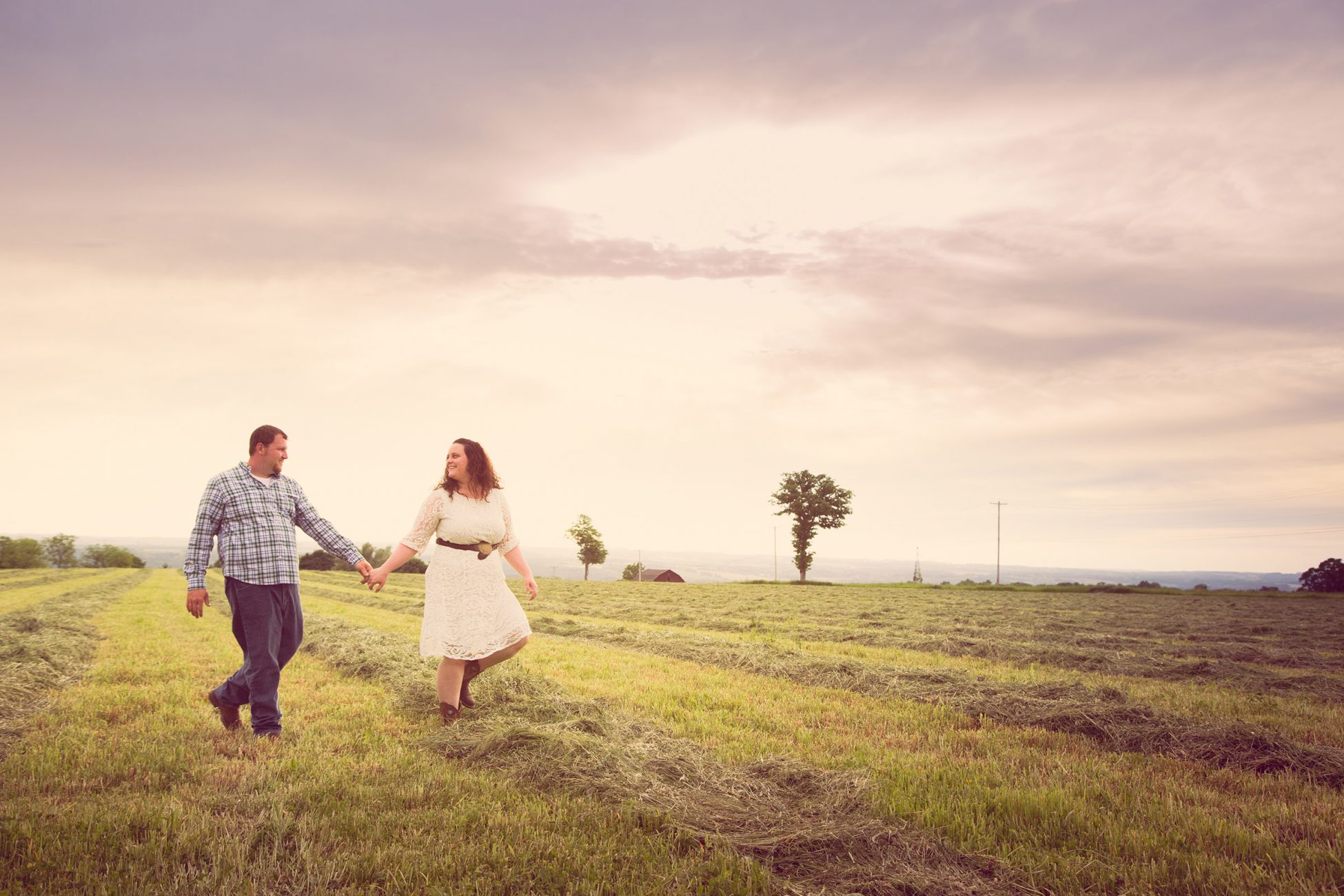 Couple walking in hay field